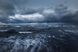 Storm clouds above the Baltic sea in winter, long exposure. Dramatic sky, waves and water splashes. Dark seascape. Germany