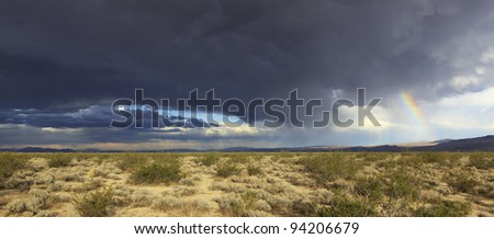 Storm clouds and a rainbow over the arid Owens Valley in eastern California - stock photo