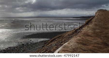 Storm clouds and sunlight along the ocean shore - stock photo