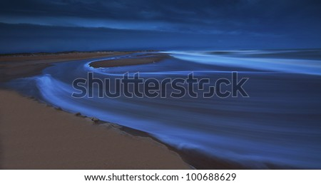 Storm clouds at twilight over sandy beach on the Atlantic shore and recessing tide