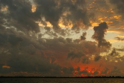 Storm clouds background. Dramatic sky at sunset with red, yellow and orange colors. The reflection of storm clouds in the sea enhances the effect