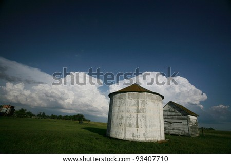 Storm clouds behind old Saskatchewan granaries