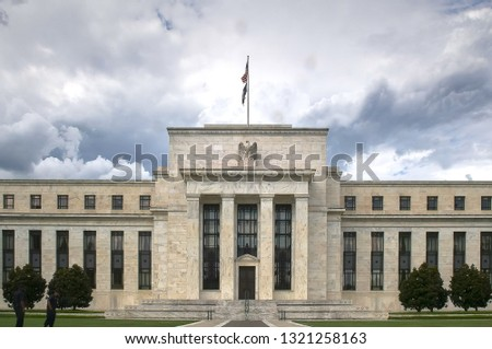 storm clouds behind the exterior of the federal reserve building