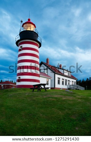 Storm clouds gather as light shines brightly of West Quoddy Head lighthouse, a red and white striped beacon in northern Maine, in New England. Tower still utilizes authentic Fresnel lens. #1275291430