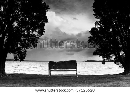 Storm clouds gathering over outdoor seat at beach - black and white.