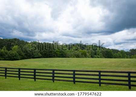 Storm clouds over a brilliant green field, black rail fence in front with treeline on the horizon, horizontal aspect
