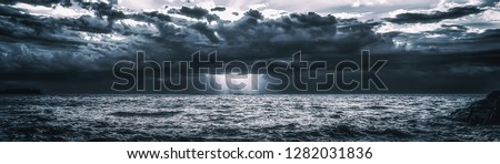 Photo of  Storm Clouds Over Cold Sea Water. Stylized panoramic seascape. Dramatic sky over Lake Superior. Great Lakes view from Keweenaw County, Michigan, USA. Wide banner background with copy space.