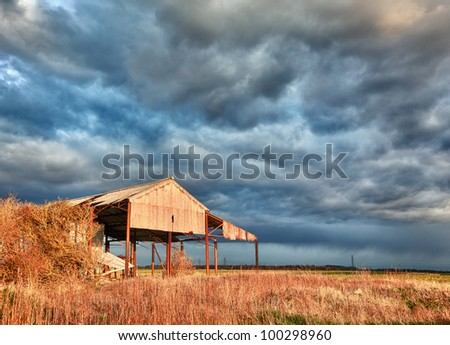 Storm clouds over sunlit deserted and ruined barn on farmland