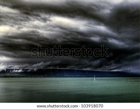 Storm clouds over the bay with sailboat taking shelter.