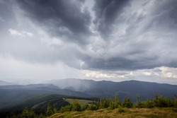 storm clouds over the mountains and small birds in a dark sky