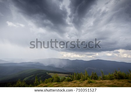 storm clouds over the mountains and small birds in a dark sky #710351527