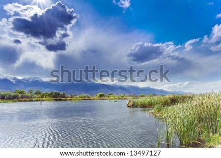 Storm clouds over the Sierra cast shadows over a pond in the Owens Valley of California