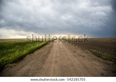 Storm clouds with a dirt road in rural America #542185705