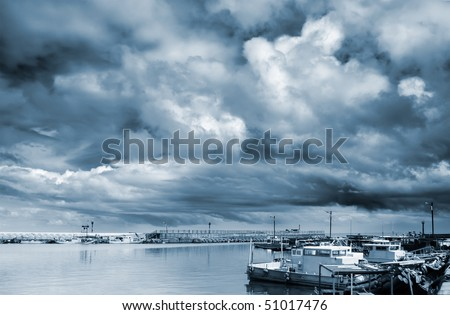 Storm clouds with boats on sea port.