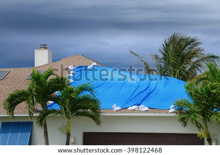 Storm damaged roof on house with a protective blue plastic tarp spread over hole in the shingles and rooftop.