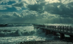 Storm on the Black sea. Pier on the shore. Restless, gloomy weather.weather. Rays of the sun through the clouds. Sea element.