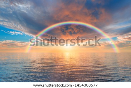 Storm on the calm sea with amazing rainbow at sunset