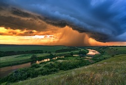 Storm overcast with thunderclouds and rain.Landscape with river and clouds at sunset