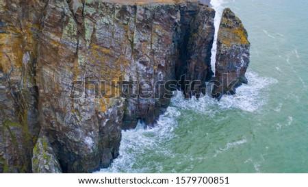 Storm sea waves break against coastal rocks. #1579700851