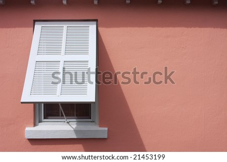 Storm shutter on pink wall of caribbean bungalow