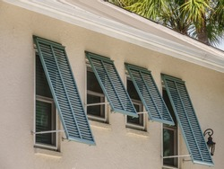 Storm shutters on side windows of a single-family house in west central Florida, USA, for themes of ventilation, climate, hurricane preparedness