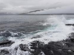 Storm waves of atlantic ocean crashing in to shore rocks in Faroe islands