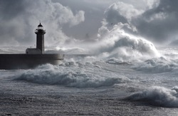 Storm waves over an iconic lighthouse in a cloudy day, Porto, Portugal.