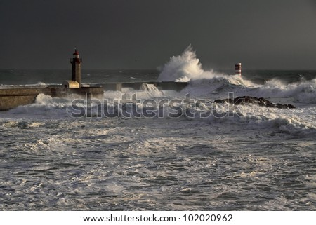 Storm waves over beacon and lighthouse of the harbor of river Douro, Portugal. Late evening light.