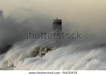 Storm waves over beacon at the mouth of the Douro River in Porto, Portugal - focus on water