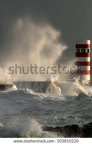 Storm waves over beacon of the harbor of river Douro, Portugal