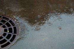 Stormwater street drain during heavy rain. Rain flowing into a stormwater sewer system.