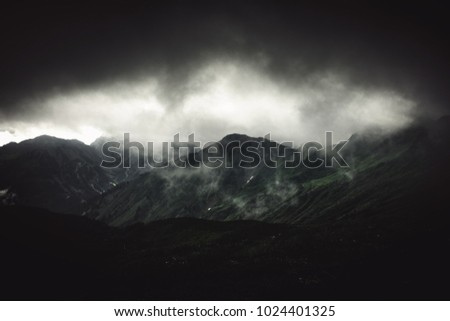 Stormy alpine landscape with fog and grey cloud under an ominous sky over rugged mountain peaks