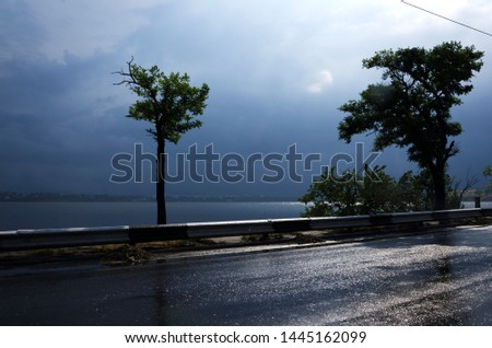 Stormy and windy weather.Dark clouds, wet road after rain, sunlights