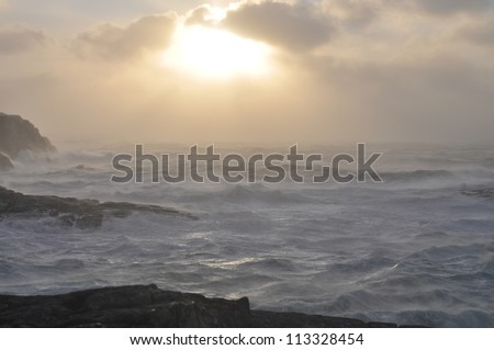 Stormy day in november on the coast of west Norway. Lagre waves and foam . Low sun can be seen  through the clouds.