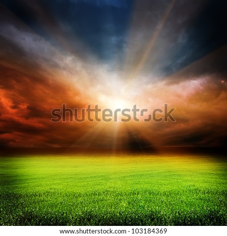 stormy evening clouds in the sky and green field of grass with sun light passing through