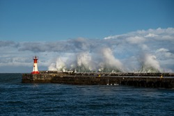 Stormy moody sea with waves crashing over harbour wall and pier and red and white lighthouse Kalk Bay, Cape Town South Africa.