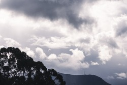 stormy moody sky with sunrays peaking through on top of the mountains in Tasmania, Australia with vegetation in the foreground
