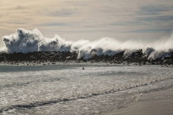 Stormy ocean at high tide, rocky beach, and silhouette of surfer, Morro Bay, California