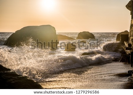 Stormy sea at sunset, the spray of the surf in the setting sun. Ischia Island, Italy.  #1279296586