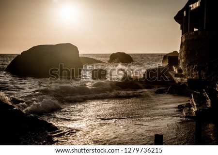 Stormy sea at sunset, the spray of the surf in the setting sun. Ischia Island, Italy.  #1279736215