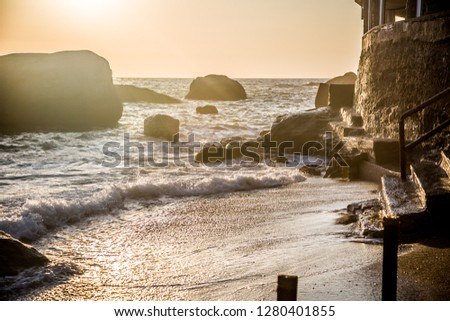 Stormy sea at sunset, the spray of the surf in the setting sun. Ischia Island, Italy.  #1280401855