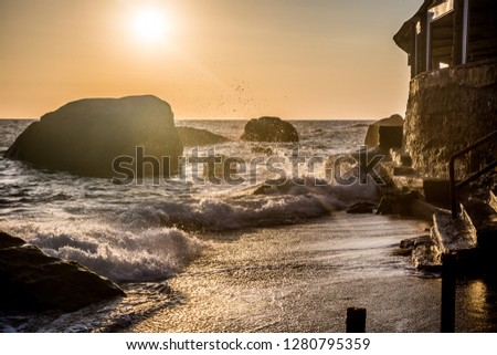Stormy sea at sunset, the spray of the surf in the setting sun. Ischia Island, Italy.  #1280795359