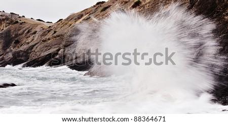 Stormy sea with crashing waves on rocks