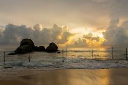 Stormy sunset in Koggala, Sri Lanka, in the water the sticks where fishermen perch.