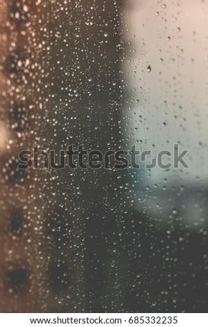 Stormy weather blur city background rain drops on window #685332235