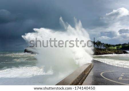 stormy weather on sea with big wave breaking on breakwater