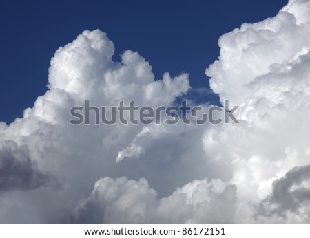 Stormy, white clouds at the blue sky