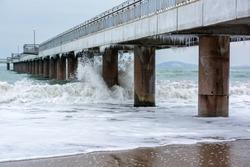 Stormy winter Black Sea, Burgas bay, Bulgaria. Winter landscape. Icicles hanging on bridge. Crashing waves.
