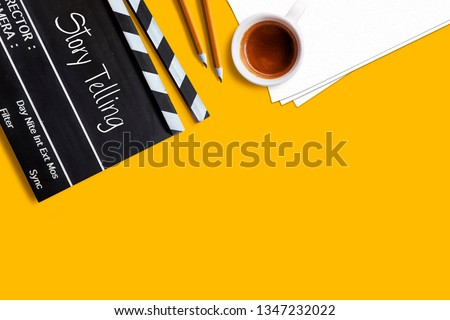 Story telling text title on movie clapper board  and coffee cup on yellow background #1347232022