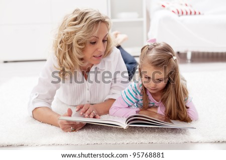 Story telling time - woman and child reading a tale book at home